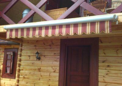 Markizy zamontowane na domku drewnianym.